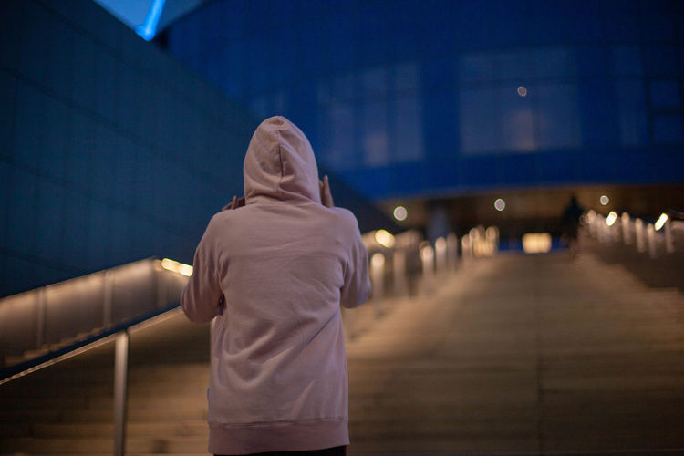Rear view of person standing on staircase at night