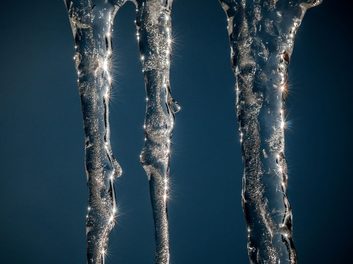 Close-up of icicles against blue sky