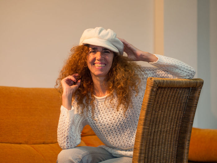 Portrait of smiling young woman sitting in hat