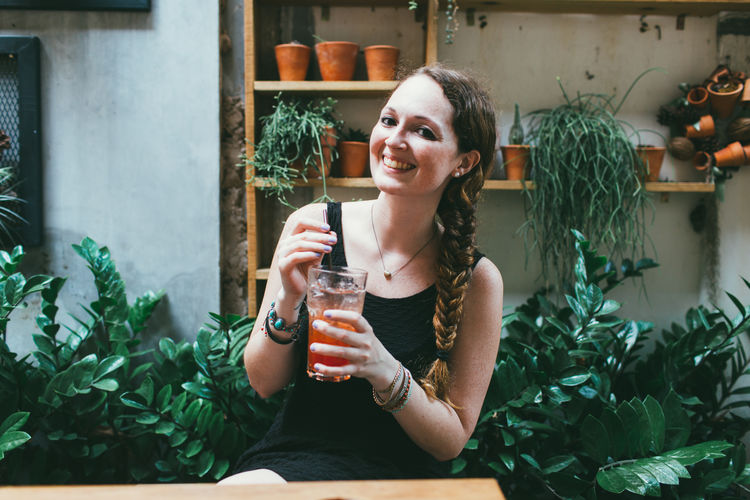 Portrait Of Cheerful Woman Having Cocktail On Table