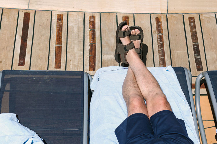 Low section of man relaxing on lounge chair during sunny day