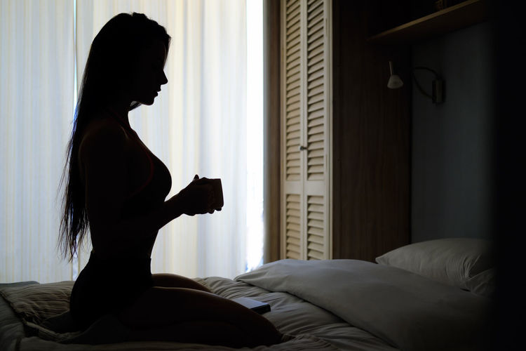 Side view of silhouette woman kneeling on bed at home