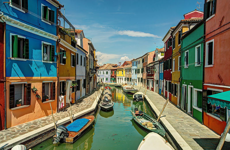 Burano, Venice, Italy - May 9, 2015: Boats dock at the edge of the sidewalk at a canal district of Burano, in the municipality of Venice. All around the houses painted in bright colors. Boats Burano Channel Colorful Italy Lagoon Mooring Road Rowing Venic Vibrant Water