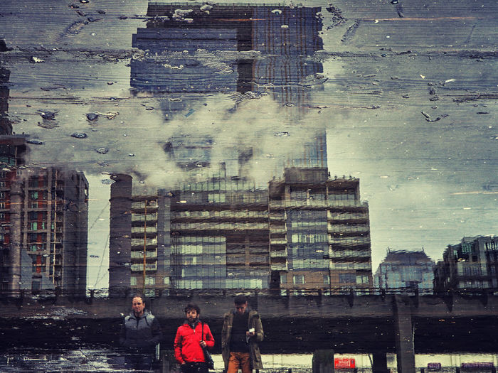 Digital composite image of people standing by buildings in city
