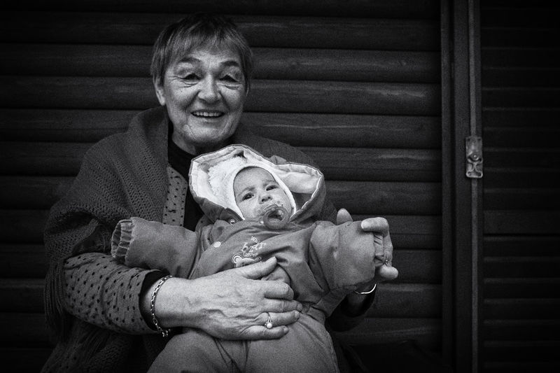 Smiling Grandmother With Baby Against Wall