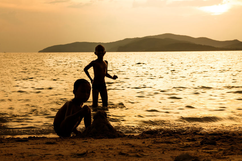 silhouette of people at the beach,The beauty of natural light at sunset. Water Real People Sunset Childhood Sky Child Beach Two People Sea Beauty In Nature Togetherness Lifestyles Boys Land Scenics - Nature Nature Men Leisure Activity Females Outdoors Innocence Silhouette Happiness Happy People Holiday Relaxing Children Women Man Romantic Orange Clouds And Sky Love Family Summer Sunrise Boy Freshair Freedom Fun