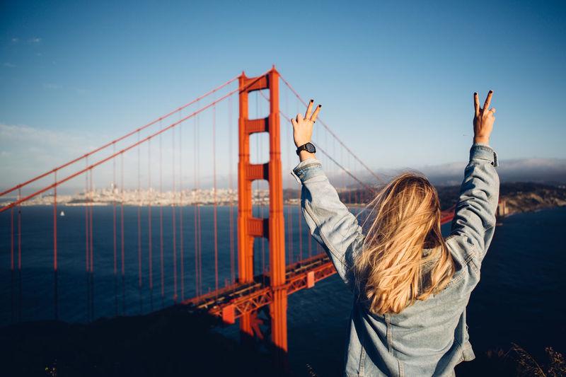 Rear view of woman gesturing by suspension bridge against sky