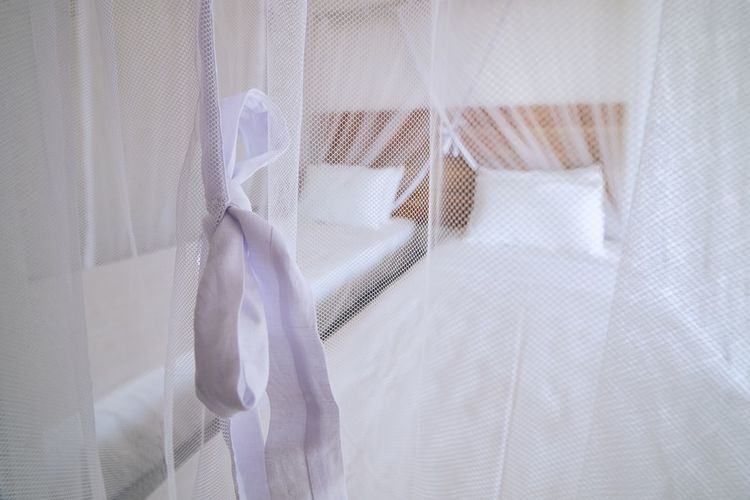 View of bed seen through white curtain