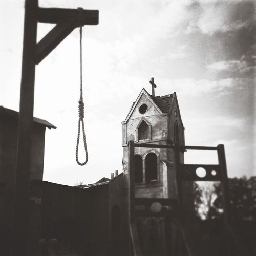 Low Angle View Of Noose By Old Church Against Sky