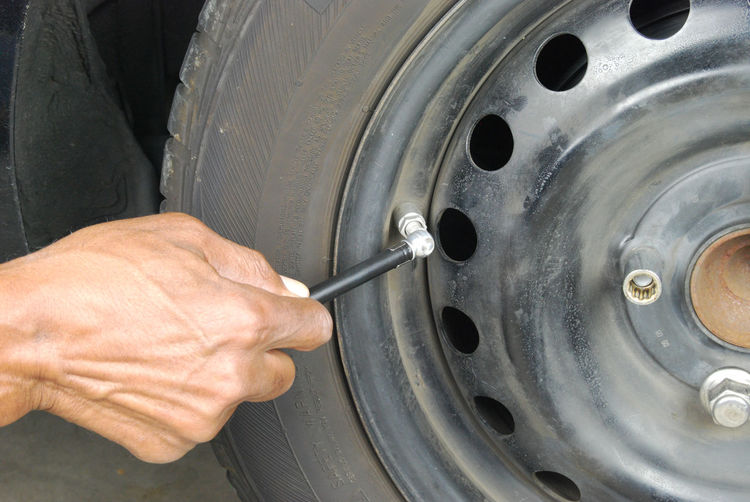 Cropped image of hand checking car tire with gauge