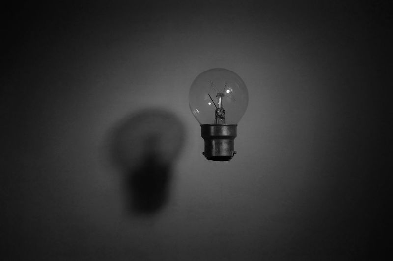 Close-up of light bulb levitating against wall