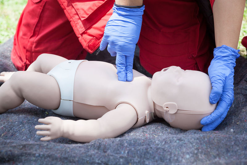 Volunteer giving first aid training with mannequin