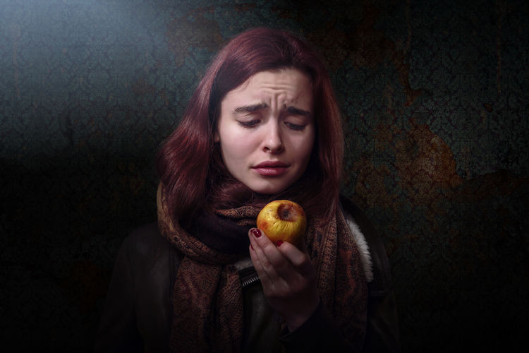 Disappointed woman looking at rotten apple against wallpaper