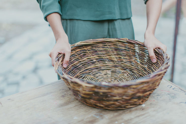 Midsection of woman holding wicker basket at table