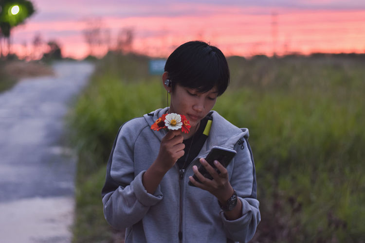 Man holding camera while standing on field against sky during sunset
