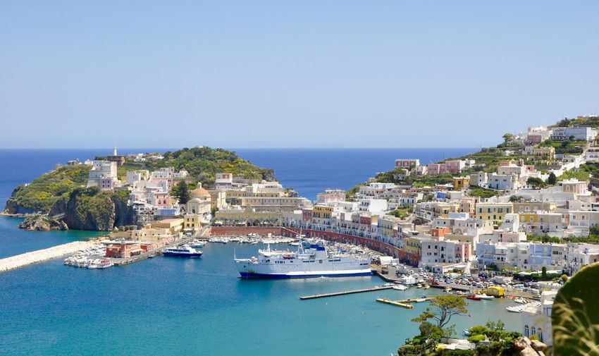 Ferry boats moored at harbor by town in ponza against clear sky