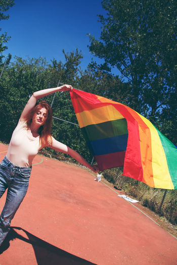 Portrait of young woman holding rainbow flag on sunny day