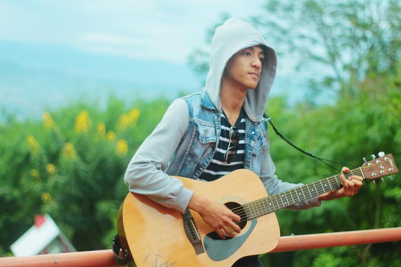 Music Lifestyles Outdoors Only Men People Guitar Musician One Man Only Music Playing Young Adult Lifestyles Plucking An Instrument Guitar Men Artist Musician Adult Cheerful Adults Only Outdoors One Person One Man Only Only Men Singing