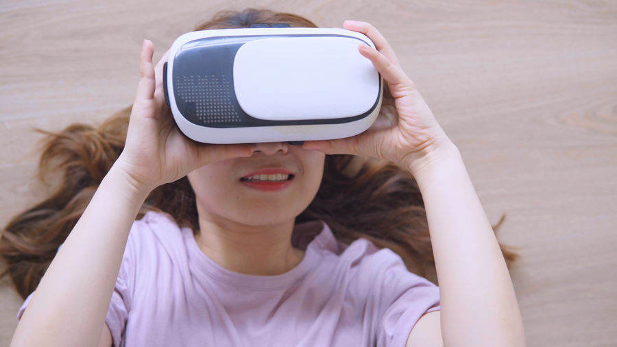 Woman gesturing while wearing virtual reality at home