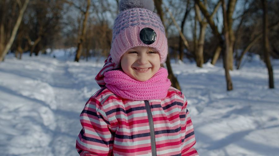 Portrait of girl in snow covered field