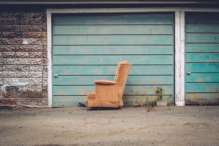 Abandoned Armchair In Front Of Wall On Street