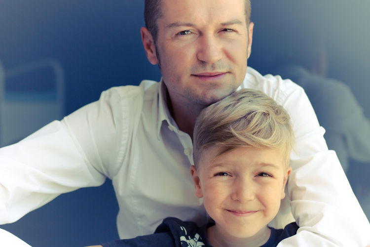 Portrait of happy father and son against wall