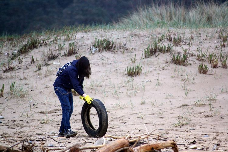 Woman Rolling Tire On Sandy Beach