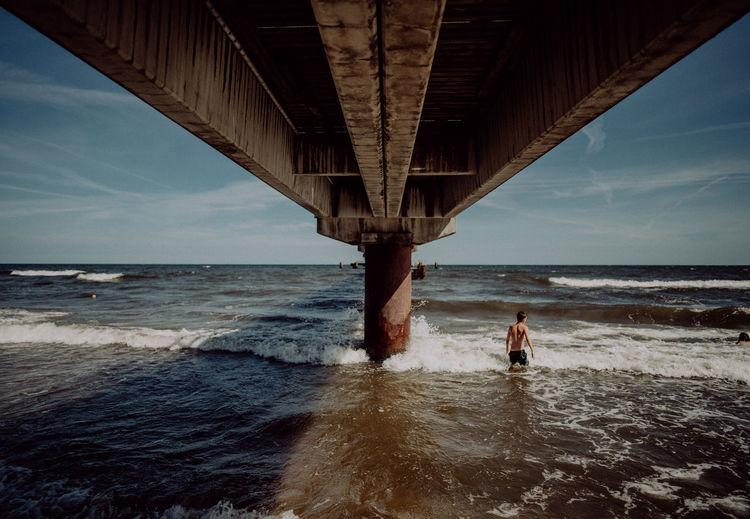 People on beach by bridge against sky