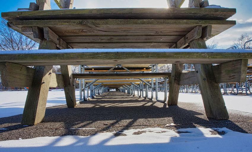 Empty wooden pier on beach against sky