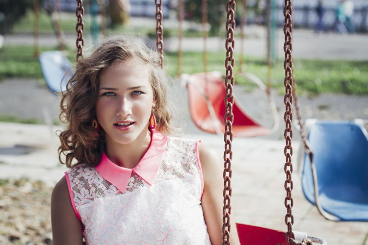 Portrait of young woman in swing at playground