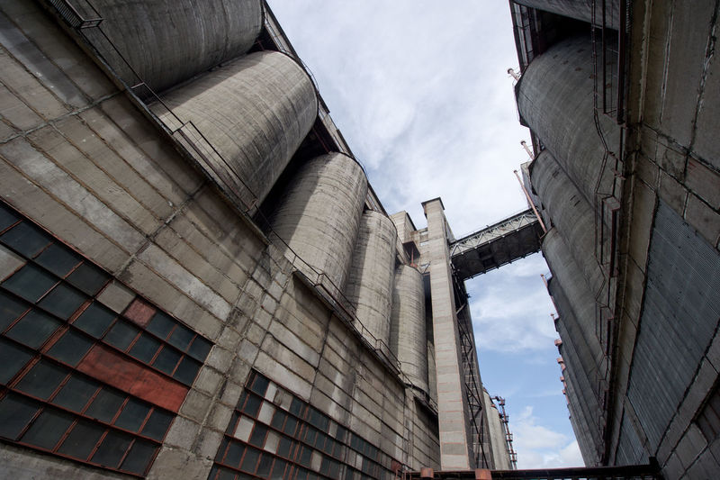Low angle view of silos against cloudy sky