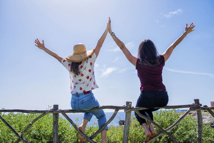 Rear view of two young woman sitting on a fence with arms raised against blue sky Sky Two People Real People Casual Clothing Human Arm Rear View Women Togetherness Leisure Activity Emotion Adult Positive Emotion Lifestyles Nature Limb Men Bonding Arms Raised Enjoyment Day Arms Outstretched Outdoors Freedom