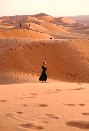 Full Length Of Woman Standing On Sand Dune At Desert