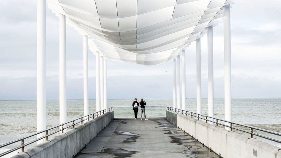 People standing on pier over sea