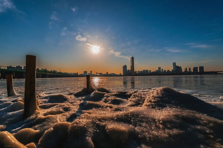 Evening sunset at the Han River in winter South Korea Architecture Beauty In Nature Building Exterior Built Structure City Cityscape Cloud - Sky Land Landscape Lens Flare Nature No People Office Building Exterior Outdoors Sea Sky Skyscraper Sun Sunbeam Sunlight Sunset Water