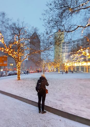 Architecture Built Structure City City Break City Life Cold Temperature Cultures Day Full Length Illuminated Lonely Outdoors People Rear View Sky Snow Tourism Travel Travel Destinations Tree Vacations Warm Clothing Winter
