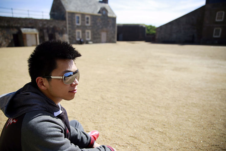 Young man sitting on sand outside historic castle