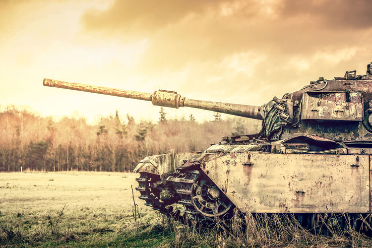Abandoned armored tank on field against sky