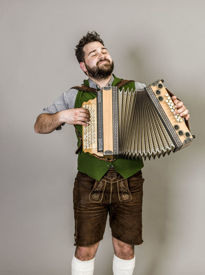 Musician Costume Leather Trousers Tradition Traditional Austria Green Pose Accordion Man Young Shorts Friendly Proud Happy Play Music Fun Joy Single One Background Copy Space Studio Entertainment Mountains Shirt STAND Hobby Leisure Cool Indoors  Front View Three Quarter Length Holding Beard Standing One Person Studio Shot Young Adult Gray Background Facial Hair Adult Mid Adult Young Men White Background Gray Mid Adult Men Looking At Camera Hairstyle