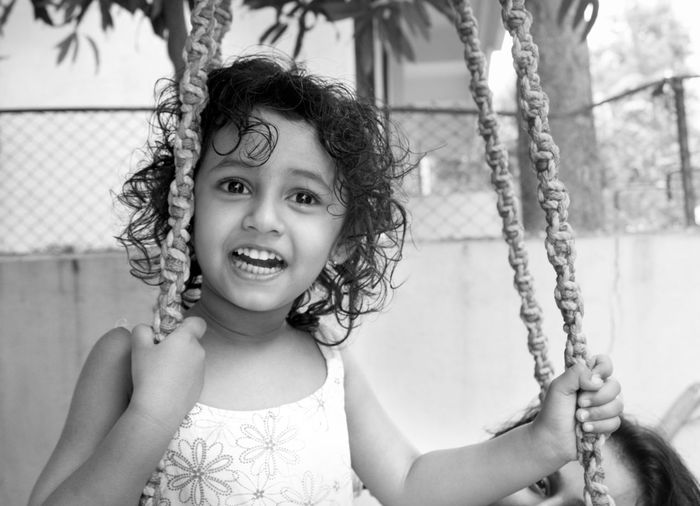 Smiling girl sitting on swing at park