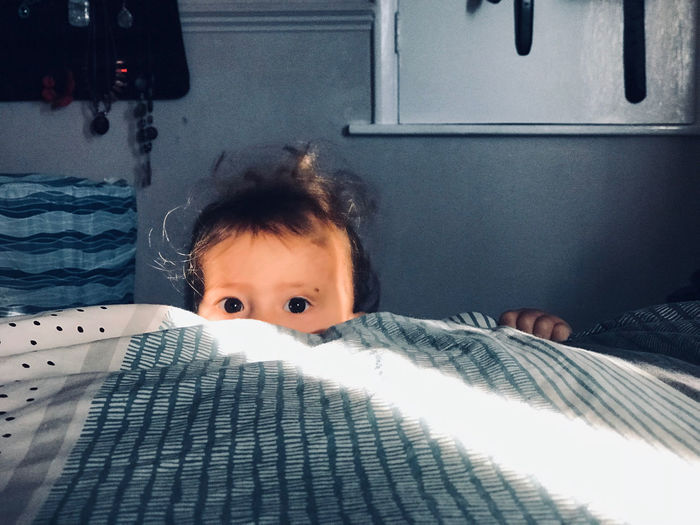 Portrait of cute baby girl hiding behind bed at home