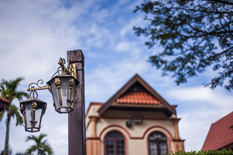 Low angle view of gas light hanging on pole against building