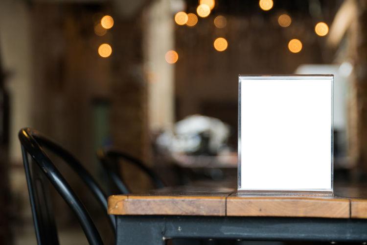 Blank Placard On Table Against Illuminated Lights