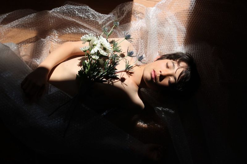 High angle view of dead boy lying with flowers and bubble wrap on floor