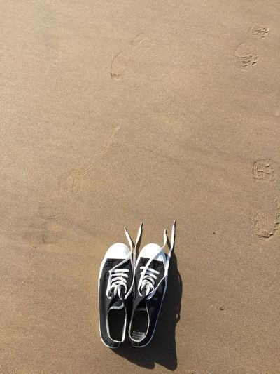 Directly above shot of canvas shoes at sandy beach
