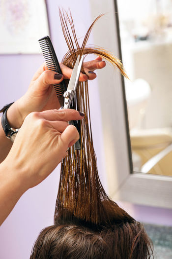 Hairdresser styling a female clients long brown hair trimming the ends with a pair of scissors, close up of her hands in a salon Cutting Hair Coiffure Comb Cutting Cutting Hair Ends Hair Care Hair Salon Hairdo Hairdresser Hairdressers  Hairstyle Haırstyle Occupation Sal Scissors Stylist Working