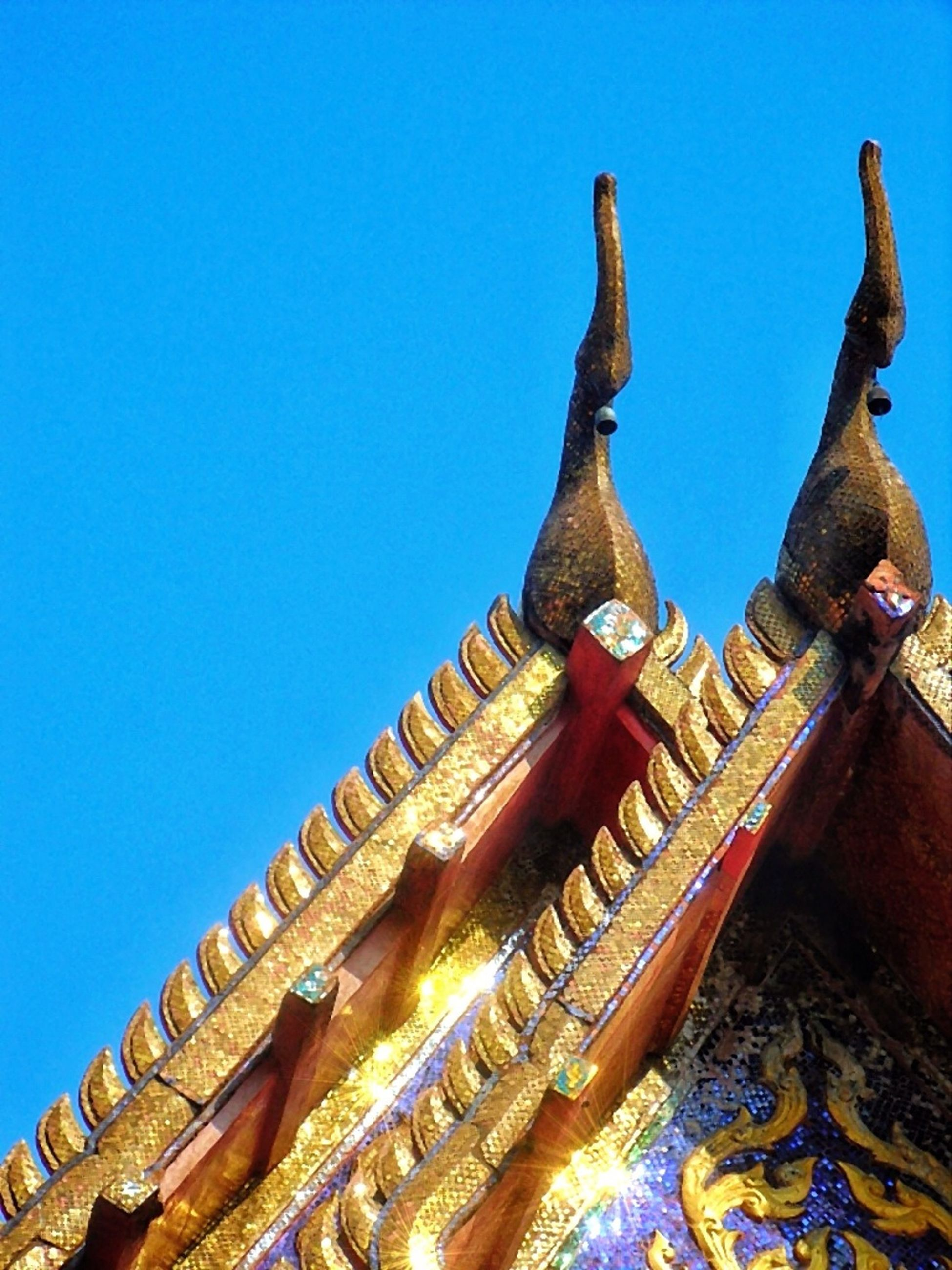 blue, clear sky, low angle view, copy space, roof, built structure, art and craft, building exterior, architecture, outdoors, art, no people, day, part of, creativity, temple - building, sunlight, religion, high section, multi colored