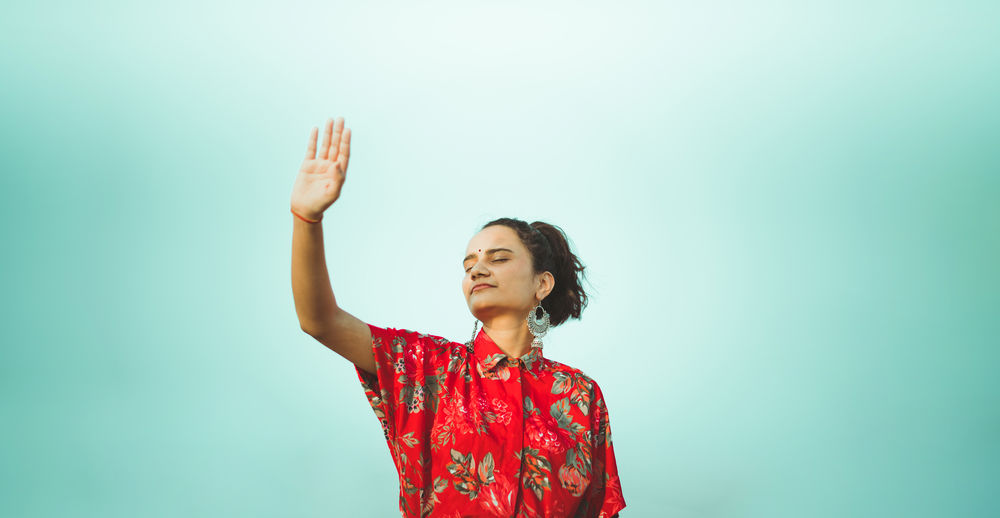 Full length of woman standing against red background