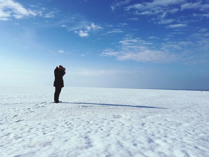 Man standing on snow covered shore against sky