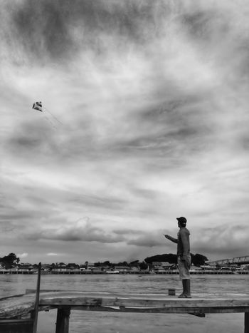 Fly With Me IPhoneography Streetphotography Blackandwhite Real People Sky One Person Cloud - Sky Leisure Activity Water Outdoors Lifestyles Nature Day Standing Full Length Men Beauty In Nature Horizon Over Water Young Adult People